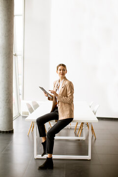 Young woman holding digital tablet in modern office