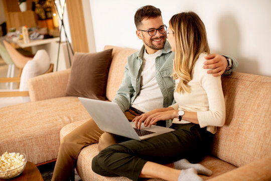 Young couple using laptop together while sitting on sofa at home