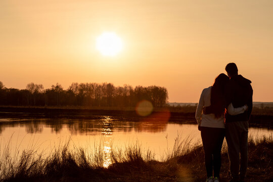 Acouple of lovers stands on the background of a sunny sunset near the river.
