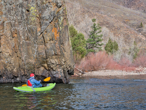 senior male kayaker is paddling a whitewater inflatable kayak on a mountain river in early spring snowstorm - Poudre River in northern Colorado