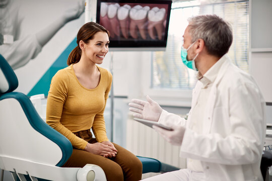 Young happy woman communicating with her stomatologist during appointment and dentist's office.