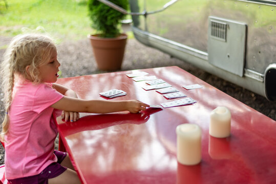 Little girl playing cards on an outdoor table at a campsite