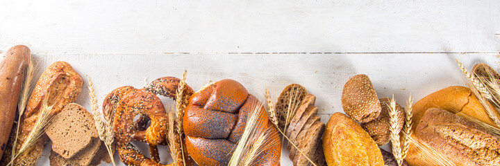Assortment of various delicious freshly baked bread, on white background top view copy space