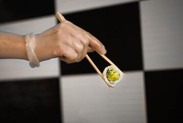 Fototapeta Sushimaster trzymający pałeczkami uramaka