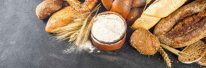 Assortment of various delicious freshly baked bread, on black concrete background top view copy space