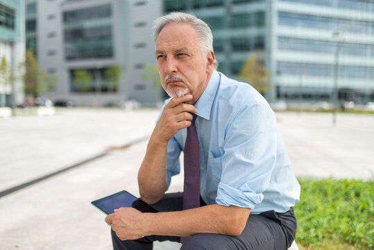 Businessman using his tablet outdoor while sitting on a bench in front of his office