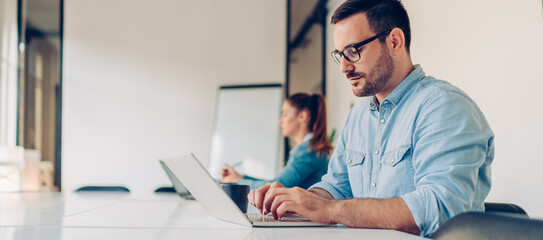 Obraz Serious focused businessman using laptop - fototapety do salonu
