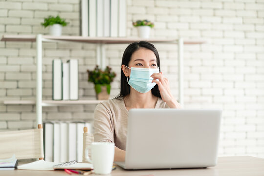 Beautiful young Asian woman wear surgical mask working from home and feeling happy smiling with joyful expression
