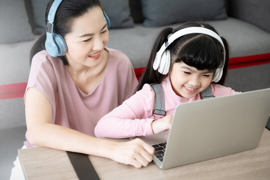 Asian girl student with parent online learning study online class video call teacher. Kid and mom wearing headset and using laptop at home