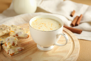 Cup with hot white chocolate on wooden background, closeup
