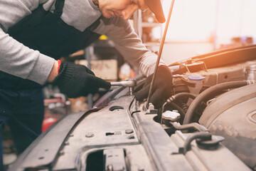 Obraz The mechanic fixing the car in the garage - fototapety do salonu