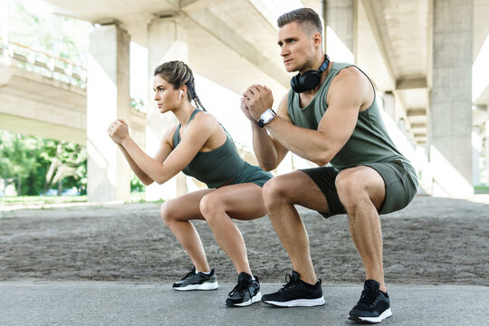 Athletic couple doing squats during street workout
