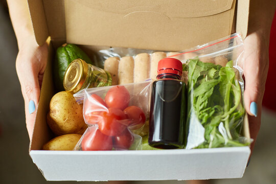 Woman hold in hand  food box meal kit of fresh ingredients order from a meal kit company, delivered, cooking at home.