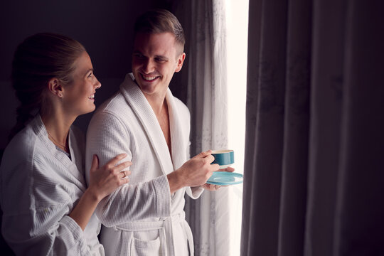 Couple Wearing Bathrobes On Romantic Hotel Or Spa Break Standing By Open Curtains With Hot Drinks