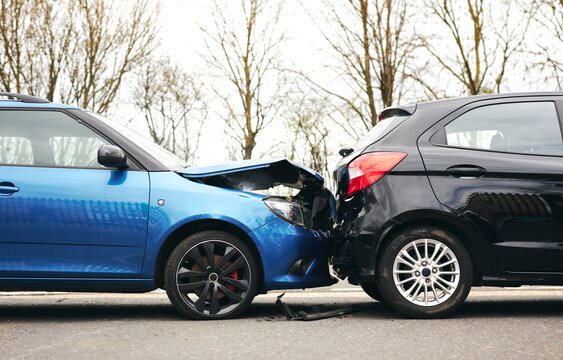 Two Damaged Cars Involved In Road Traffic Accident Showing Smoke After Collision