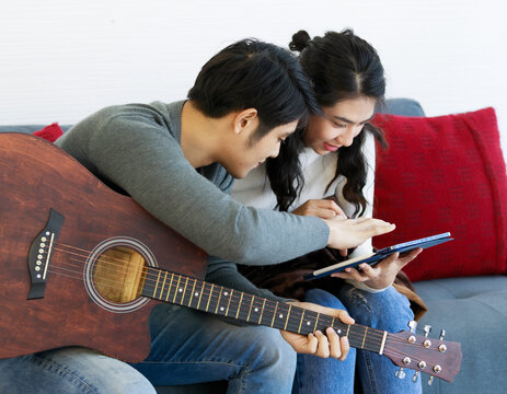 Side view portrait of cute smiling young Asian lover couple in white and gray long sleeve sweatshirt and blue jeans sitting on the sofa while playing acoustic guitar and singing a song with happiness