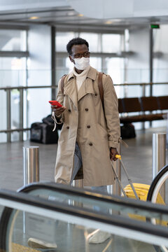 Afro-American traveler man with yellow suitcase goes to escalator in airport terminal, wear face medical mask to protect yourself from contact with flu virus, pandemic covid-19. New normal concept