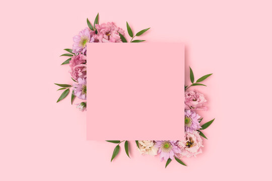 Empty square paper card with border frame made of eustoma flower on a pink pastel background. Springtime concept.
