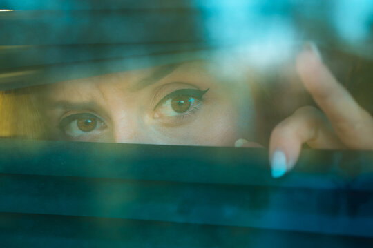 Woman in quarantine looks through blinds outside window. Self-isolation concept.