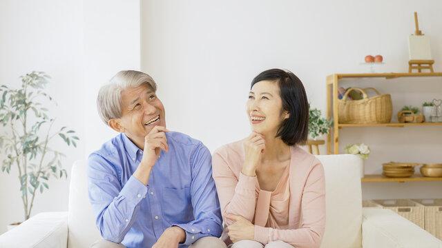 リビングで考え事をする中高年夫婦