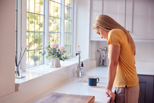 Depressed And Unhappy Mature Woman At Home Standing By Kitchen Window