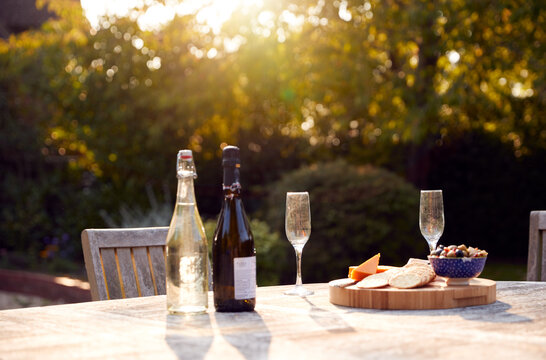Outdoor Table In Garden At Home Laid With Champagne And Snacks