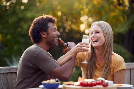 Mature Couple Link Arms Celebrating With Beer And Champagne Sitting At Table In Garden With Snacks