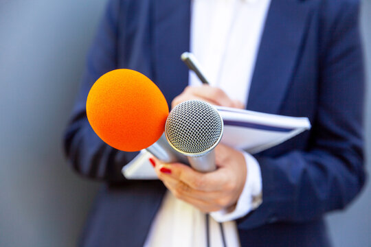 Microphone in focus, female journalist at press conference writing notes. Public relations (PR) concept.