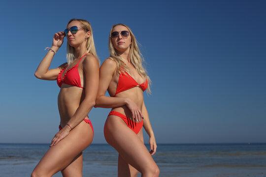 young women girlfriends in bikini on a beach