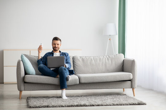 Relaxed man with laptop sitting on couch at home