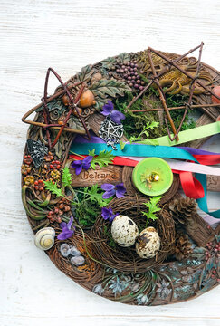 Wiccan altar for Beltane sabbath. spring pagan festive ritual. wheel of the year with colorful ribbons, candle, flowers, pentagram - symbol of Beltane celtic holiday, spring season.  flat lay