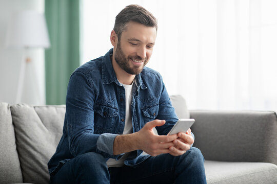 Cheerful middle-aged man sitting on sofa with mobile phone