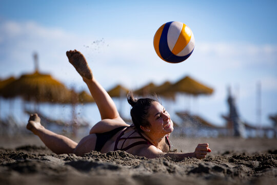 young women playing beach volleyball on a sunny day
