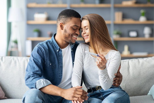 Becoming Parents. Romantic Multiracial Spouses Holding Positive Pregnancy Test At Home