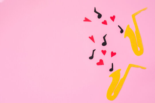 A cutted out of felt saxophones from which hearts and melodies flew out, on a pink background. Flat lay. International Jazz Day. Copy space