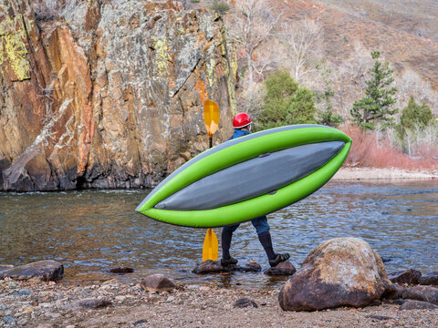 male kayaker is carrying a whitewater inflatable kayak on a shore of mountain river in early spring - Poudre River in northern Colorado