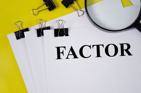 factor word written on white paper and yellow background with magnifier. word
