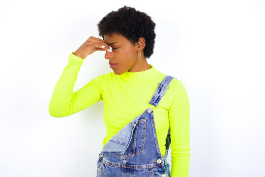 Sad African American female with curly bushy wears jeans overalls over white wall suffering from headache holding hand on her face
