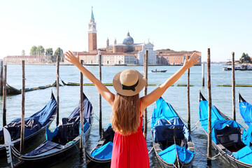 Holidays in Venice. Back view of beautiful girl with raised arms up enjoying view of Venice Lagoon with the island of San Giorgio Maggiore and gondolas moored.