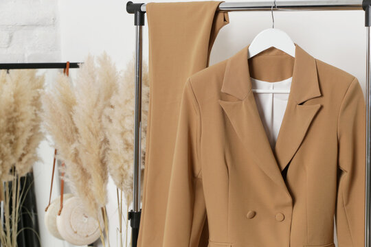 Corner in fashion atelier with fashionable tailored blazer hanging on a rack. Modern premium quality hand made woman's fashion.