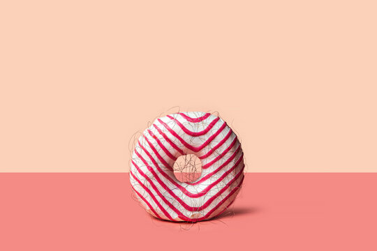 Epilation concept - donut with hair on a pink background