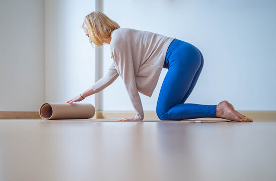 Young woman laying down mat to do yoga at home.