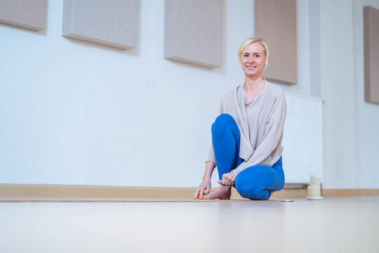 Full body portrait, of a female yoga instructor, sitting in the training room. She looks to the camera smiling, with a serene expression.