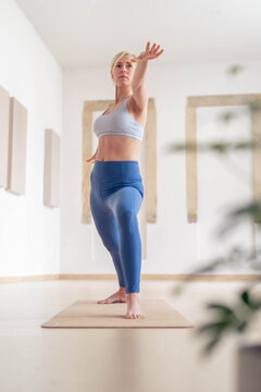 Vertical photo of an adult woman, doing yoga poses, in her empty studio, closed for Covid 19.