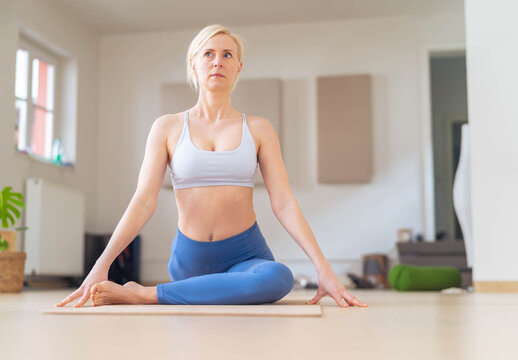 Close-up of a woman doing yoga in her cluttered home.