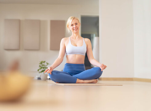 Young woman stretches, after a yoga session, in her empty studio, closed for the corona virus. Looks at the camera smiling