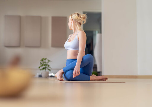 Young woman stretches, after a yoga session, in her empty studio, closed for the corona virus.