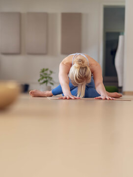 Vertical Shoot of a Young woman stretches, after a yoga session, in her empty studio, closed for the corona virus.