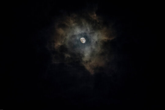 The moon shining through rain filled clouds where the moonlight creates colors as it is reflected through the drops.
