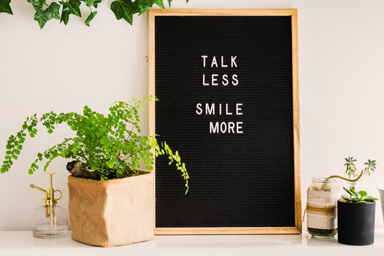 letterboard with the message, talk less smile more